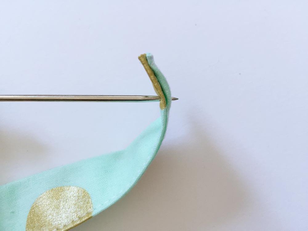 Stoff vorsichtig mit einer Nadel beiseite schieben